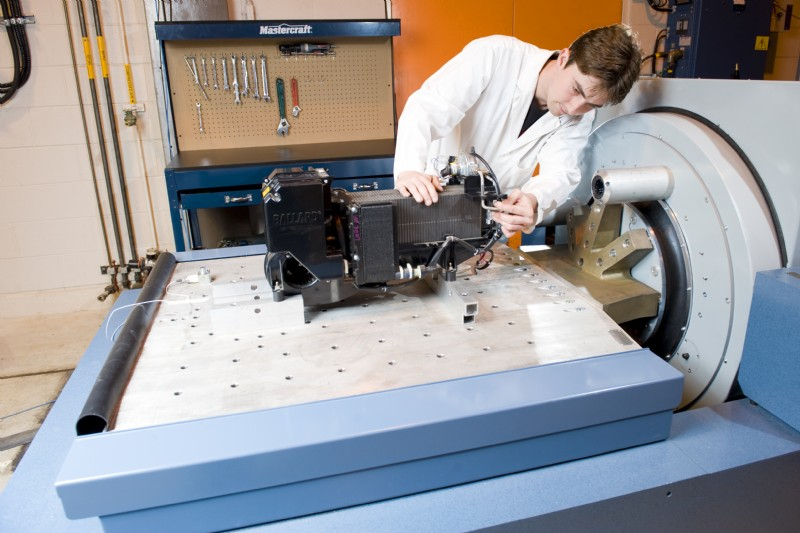 A technician inspects a fuel cell undergoing vibration tests on a R16 shaker